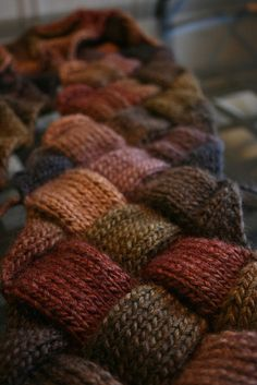 Recycle Old Sweaters by using rug braiding techniques. (OR could I tunisian crochet narrow stitch samples and weave them together into squares?)