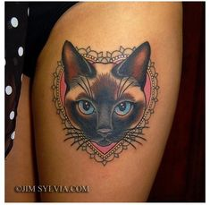 Cute cartoon like colored cat portrait tattoo on thigh - Tattoo.pm