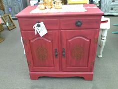 SOLD - Stenciled red cabinet - This solid wood cabinet has a single drawer and two doors below that open to shelving. It has been painted red, door fronts stenciled, dark wax finish with new iron hardware. ***** In Booth A8 at Main Street Antique Mall 7260 E Main St (east of Power RD on MAIN STREET) Mesa Az 85207 **** Open 7 days a week 10:00AM-5:30PM **** Call for more information 480 924 1122 **** We Accept cash, debit, VISA, Mastercard, Discover or American Express
