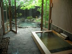 indoor in-ground tub on rock/natural surface facing full-panel glass bifold doors outdoor tub/pond & lots of greenery - feels like secluded oasis Japanese Bath House, Japanese Spa, Japanese Style House, Japanese Bathroom, Outdoor Tub, Outdoor Baths, Outdoor Bathrooms, Dream Bathrooms, Casa Steampunk
