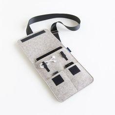 Pochette en feutre gris chiné. Bandoulière réglable façon ceinture de sécurité. Un poche pour tablette, deux poches à téléphone portable, 2 boucles en velcro pour cables et oreillettes. Fermeture par scratch.