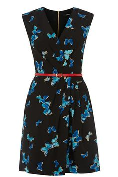 Turn heads in this bold blue butterfly printed dress. The piece features a flattering wrap front and a v neckline. The piece features slight cap sleeve styling and a skinny contrasting coral waist belt.