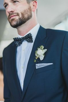 Navy blue suit with white boutonniere.