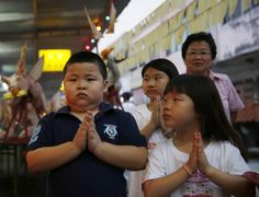 Children pray during the Hungry Ghost festival in Kuala Lumpur August 3, 2014. According to Taoist and Buddhist beliefs, the seventh month of the Chinese Lunar calendar, known as the Hungry Ghost Festival is when the Gates of Hell open to let out spirits who wander the land of the living looking for food. Food offerings are made while paper money and incense sticks are burnt to keep the spirits of dead ancestors happy and to bring good luck. REUTERS/Olivia Harris