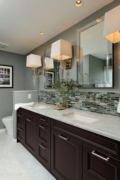 This gray contemporary bathroom features a double-vanity design with a Carrera marble countertop, glass-tile backsplash, and polished chrome sconces and fixtures. The sleek mirrored medicine cabinets add storage and polish to the space. by earnestine Dark Wood Bathroom, White Bathroom, Back Splash Bathroom, Bathroom Marble, Glass Tile Backsplash, Vanity Backsplash, Backsplash Ideas Bathroom, Backsplash Cheap, Quartz Backsplash
