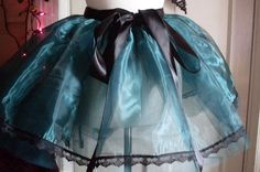 "Teal wrap around Organza Tutu made with two layers of Teal Dress net and trimmed with Black Lace, finished with a Black Satin waist Ribbon..  Size Teen - Adult  waist up to 43""  length 16"""