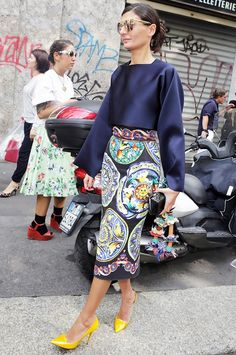 Giovanna Battaglia wearing a silk navy blouse, printed pencil skirt, and bright yellow pumps.