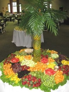 If you have a Destination Wedding and not everyone can attend, consider throwi9ng a Celebration Party when you get back and recreate a tropical decor, put up a big screen that automatically shows pictures from the wedding, have palm trees, tropi al drinks and food, etc like this wedding fruit display - Pineapple Tree w/ Fruit Display