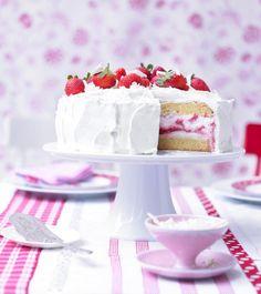 Zwischen die Eierlikör-Biskuitböden der Torte schichten sich Quark und Erdbeerpüree. Die Sahnehülle wird mit weißen Schokospänen verziert.