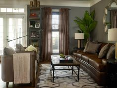 A geometric rug provides a pattern base to decorate the solid surfaces and neutral tones of this transitional living room. A brown leather sofa and taupe chairs face a wood coffee table with wrought iron legs. Sheer curtains add decoration to the windows while still allowing natural light to enter the room.