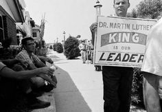 Dr martin luther king jr gives a young picket a pat on the back as