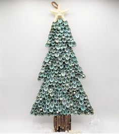 """Beach Christmas decor shell Christmas tree wall hanging. Our gorgeous aqua limpets meticulously hand cover a wooden Christmas tree base, looking like the fronds on a pine tree.  The trees trunk is made using cool real sea urchin spines, and the tree topper is a textural white knobby starfish.  Just a few pearls for some added bling!  Classic, pretty for year-round use, and lots of coastal Christmas charm.  There is a jute hanging loop from the back. Just perfect and sweet.  19.5 x 10""""."""