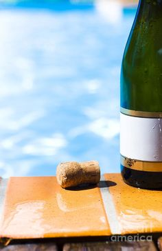 Green champagne bottle with a blank gold rimmed label and a cork standing on wet tiles alongside a sparkling blue swimming pool in a summer party concept by Ryan Jorgensen