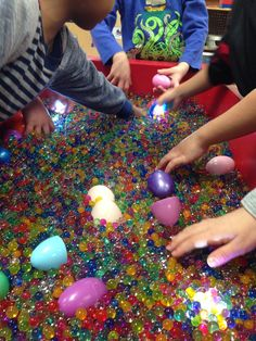 Pre-K Sensory table filled with rainbow water beads, LED waterproof lights, and plastic colored Easter eggs :)