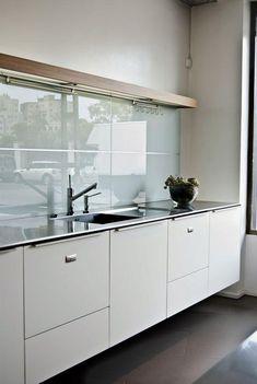 Cocina con muebles blancos y encimera de acero inoxidable