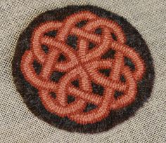 """Celtic Knot by Christine Little. 6"""" diameter. knot was hooked in #4 and background plaid in #5. Plaid was a gray and orange colour"""