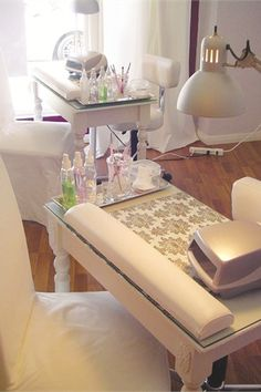 Each manicure station features a collection of treatment products, a UV light for curing, and an ergonomic wrist pad. Although the stations have an overhead light, an abundance of natural light streams in from the salon's floor-length windows.