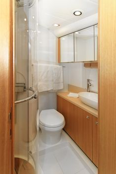 Compact yacht bathroom appointed with warm natural wood cabinetry and glass shower frame, white tile, and oval vessel sink.