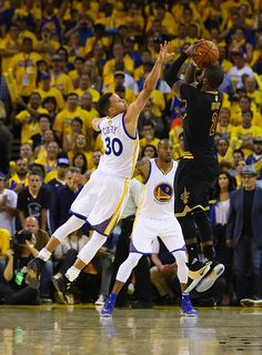 Kyrie Irving of the Cleveland Cavaliers shoots a threepoint basket late in the fourth quarter against Stephen Curry of the Golden State Warriors in...