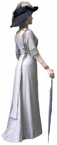 """Pale blue woolen dress with a hobble skirt and Bucks point lace trim at the neck. She is also wearing a black straw """"merry widow"""" hat trimmed with ostrich plumes and a hair work bracelet. She carries a silk umbrella."""