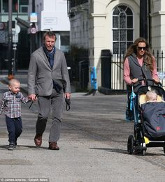 Family trip: Guy Ritchie looked as though he did not have a care in the world as he enjoyed a morning stroll with his wife Jacqui and their brood in London on Sunday morning