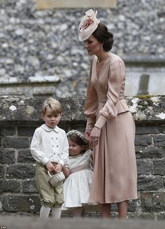 Kate stands with Princess Charlotte and Prince George, who were flower boys and girls at t...