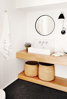 Black and white bathroom with wicker baskets, a thin black mirror, and wood sink base: