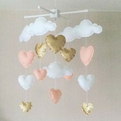 Clouds and hearts baby crib mobile. An ideal gift for a new babys nursery or for room decor in an older childs bedroom. This mobile consists of five white clouds and twelve hearts (Gold, pale coral and white) in three sizes. The elements are suspended with white thread from either a