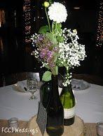 Wedding reception centerpieces.  Baby's breath in wine bottles.
