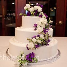 The couple went for an old-fashioned buttercream cake with little decoration other than a cascade of white and purple blooms.