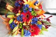 bright colorful wedding bouquet red, yellow, blue flowers