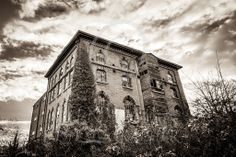 Rundown building in the heart of town. Old mill in black and white with a moody sky, undergrowth growing around it with ivy creeping up the side. Old Building, Storyboard, Large Prints, Art For Sale, Art Gallery, Louvre, Earth, Sky, Black And White