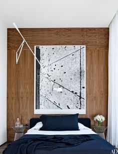 At the home of Alex Rodriguez, a walnut-paneled guest room displays a large Adam McEwen work. | archdigest.com