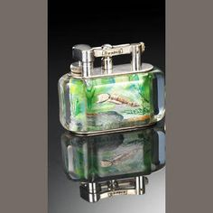 """DUNHILL: An 'Aquarium' lighter, electroplated mounts, Perspex body, engraved and painted , one side depicting a silver, red and black fish, the other depicting two gold and red fish, on a light green ground, amongst water plants and rocks, incuse stamped to base """"Made in England"""", in a cardboard presentation box, length 9cm, width 4.5cm."""