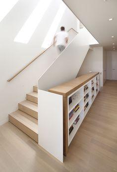 Detalles arquitectónicos limpios hechos a medida: baranadilla, estantería y escalera de madera y color blanco. Minimalismo