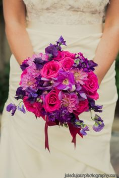 A bold bridal bouquet of hot pinks and purples, flowers included are hot pink roses, fuchsia dendrobium orchids, purple sweet peas, lavender dahlias, purple mokara orchids and purple stock. This beautiful wedding was held at Christ Church Cathedral in New Orleans, followed by reception at Broussard's Restaurant.