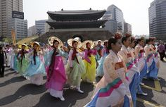 On May 4, 2013, South Korean women wearing the traditional Hanbok march on the street in front of the newly-rebuilt landmark Sungnyemun Gate, or Namdaemun Gate, during its reopening ceremony in Seoul.