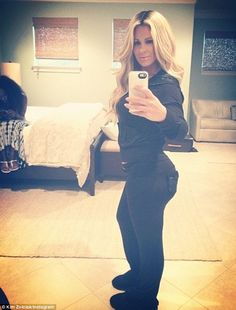 Never too many selfies?: Kim Zolciak could not help but take yet another snap of herself in a mirror on Sunday even while her friend Sweetie Hughes was 'trying to make her work'