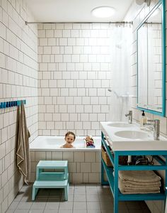 In a Brooklyn brownstone renovation, a mostly white bathroom receives some pops of blue color from a series of towel hooks, a step stool, an under-sink storage unit, and a large frame around the mirror.  Photo by: Matthew Williams