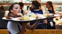 Eine Kellnerin trägt ein Tablett mit mehreren Gerichten. (dpa / picture alliance)