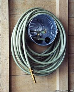 """A galvanized paint bucket makes a practical and inexpensive caddy for a garden hose and sprinkler.  Drill three holes in a triangular pattern in the bottom of the bucket. Depending on your wall, bolt or screw the bucket to the wall; strengthen the cut edges of the holes with washers.  See the """"Bucket-Hose Storage"""" in our  gallery"""