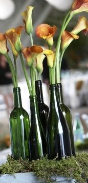 beautiful flowers in old fashion green bottles on moss. The are decorations for a wedding