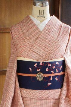 クリームベージュ色の地に、ピンクとディープレッド、テラコッタブラウン、カフェオレブラウンの色糸で、ナチュラルキュートなチェック模様が織り出された単着物です。