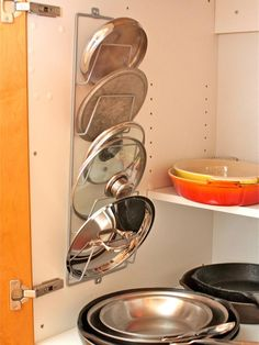 Getting all those pot lids in line is a snap with this organization idea from Aimee Wimbush-Bourque. Just screw a metal magazine rack into the back of a cabinet door and arrange lids by size. The sleek design not only makes it easy to find the right lid but also opens up some additional cabinet space, too.