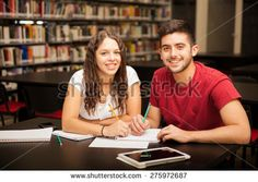 Portrait of a cute young brunette with curly hair studying with her boyfriend in the library and smiling - stock photo