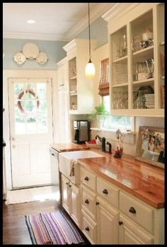white cabinets, butcher block countertops, farmhouse sink and pretty blue walls by tulasi.fanelli
