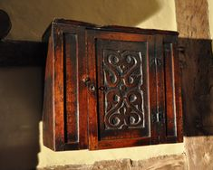 CHARLES II OAK AND ELM HANGING MURAL CUPBOARD. ENGLISH. CIRCA 1680.  THE CENTRAL STRAPWORK CARVED DOOR WITH ORIGINAL BUTTERFLY HINGES AND LOCK, FLANKED BY PLAIN PANELS. THE TOP, SIDES AND BACK ARE MADE FROM ELM.