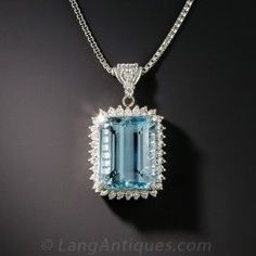 A beautiful deep sky blue emerald-cut aquamarine, weighing 6.07 carats, glistens and glows from within a sparkling halo of small bright-white round brilliant-cut diamonds in this classic estate jewel crafted in platinum. 7/8 by 1/2 inch with adjustable 17 1/2 inch platinum chain.
