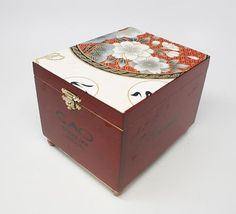 An old cigar box completely transformed into a jewelry, keepsake or treasury box. The top and the bottom of the box are covered with an asian motive fabric with floral design. The inside of the box is bordered with burgundy color velvet damask paper.