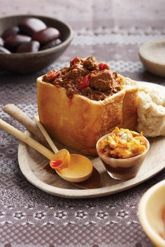 BUNNY CHOW aka BUNNY aka KOTA ~~~ bunny chow is a fast food dish consisting of a hollowed out loaf of bread filled with curry. this post's link will lead you to a lamb version of this beloved dish. South African Dishes, South African Recipes, Indian Food Recipes, Africa Recipes, Curry Recipes, Beef Recipes, Cooking Recipes, Recipies, Kos